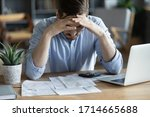 Small photo of Sad depressed man checking bills, anxiety about debt or bankruptcy, financial problem, bank debt or lack of money, unhappy frustrated young male sitting at work desk with laptop and calculator