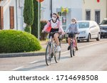 Small photo of Manzano, Italy - 25.04.2020: Little Italian city during the quarantine. The first steps to loosen coronavirus restrictions. Two girls ride bicycles in protective masks in the street in Manzano, Italy
