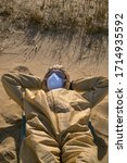 Small photo of Beach life in age of coronaviruses. Man in protective suit, mask and glasses is sunbathing on sand. How will life change after Covid-19 - changing social paradigm concept