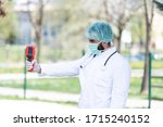 Doctor Man Use Infrared Forehead Thermometer Gun to Check Body Temperature for Virus Covid-19 Symptoms With the Isolation Gown or Protective Suits and Surgical Face Masks Outside in Park - stock photo