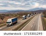 Convoy of transportation  trucks in line as a caravan or convoy on a country highway under an amazing blue sky