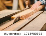 Small photo of Closeup of wood cutting table with electric circular saw. Man skilled cabinet maker using circular saw at woodworking workshop. Professional carpenter cutting wooden board at sawmill. Sawing machine