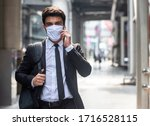 Small photo of Businessman walking in city with very small amount of people during covid-19 outbreak make phone call and wearing white mask