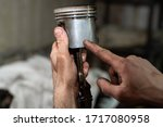 Small photo of Cars piston in hand close up. Old car piston have scratch and abrasion. Piston in old oil. Hand indicates a damaged area.
