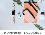 Small photo of A beautiful flat overlay of a home office with a modern smartphone, smartwatch, wireless earphones, notepad and pens. Pink and blue colors. Copyspace to write. Minimalist style to enhance productivity