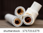 Small photo of Old broken sludge polypropylene plumbing pipes with red rust and limescale. Corrosion, sludge and hard water concept. Rust broken water pipes