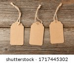 Small photo of Empty brown paper tag tied with white string. Price tag, gift tag, sale tag on the gray wooden background, close up