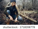 Woman tourist cuts wooden stick with knife in forest. Bushcraft Survival and Scouting Concept - stock photo
