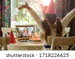 Small photo of Happy little girl celebrating birthday at home with parents and grand parents on video call. Laptop with senior couple online, cake with candles on table.