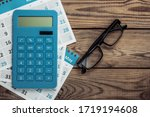 Small photo of Calculator with sheets of the monthly calendar, glasses on wooden background. Economic calculation, costing. Top view