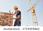 Installing brick wall. Construction worker in uniform and safety equipment have job on building. - stock photo