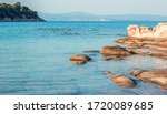 peaceful rocky beach shore line of Mediterranean sea bay shore scenic view in summer day time in July month with background horizon line  - stock photo