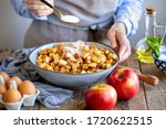 Small photo of Add sugar to the pie filling. The girl pours sugar into the apple strudel filling. Sugar sprinkles from a spoon into a bowl. Girl in an apron cooks in the kitchen. Ready apple Viennese strudel at home