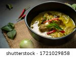 Small photo of Hot Thai chicken green curry or Kiew Wan curry on table with spices & herbs. Thai Chicken green curry is a tasty traditional Thai food made from coconut milk & green curry paste. Thai food concept.