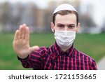 Small photo of Handsome young Jewish guy in traditional jewish male headdress, hat, boom, or yiddish on head. Man in medical mask on his face showing palm, stop sign against coronavirus, virus pandemic. Covid-19