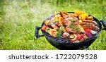 Small photo of Assorted delicious grilled meat with vegetables on barbecue grill with smoke and flames in green grass