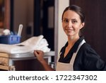 Small photo of A portrait of a smiling hotel maid with a cleaning cart and clea