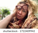 Small photo of A middle age woman seems to be totally overwhelmed with whatever is going on. Her eye glasses are misplaced and her face expression is weird and funny