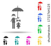 father holds an umbrella over...