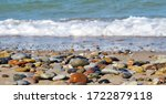 Colored Pebbles On A Sandy...