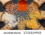 Different type of raw dry legumes composition. White beans, lentils, bulgur, chickpeas, kidney beans, corns, rice, in burlap sack Mix organic legume concept