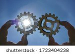 Small photo of Male hand holding three wooden cog gear wheel on sunny sky background. sunshine and blue sky . sun rays.one part of whole. symbol of association and connection. business strategy