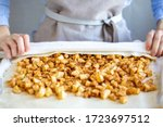 Small photo of Hands wrap the dough with apple filling make apple strudel.Girl is preparing a pie at home in an apron.Work with puff pastry.The process of making apple strudel.Mom makes a pie.Apple strudel roll