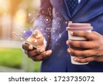 Small photo of Close up of african businessman holding coffee to go and using brand new mobile phone with functional icons