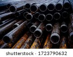 Small photo of Oil Drill pipe. Rusty drill pipes were drilled in the well section. Downhole drilling rig. Laying the pipe on the deck. View of the shell of drill pipes laid in courtyard of the oil and gas warehouse