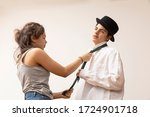 Small photo of Girl knots the tie of the boy getting ready for work from home. He is listless
