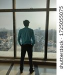 Small photo of Young Indian man standing by the window enjoying the view during a hectic working day