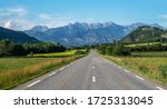 A long straight road leading towards a mountains in France. Amazing bright colorful spring and summer landscape. Yellow fields of flowering rape and blue sky with clouds. Natural landscape, Europe. - stock photo