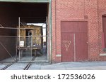 Abandoned WWII factory with train tracks and old train behind chain link fence located in Martinsburg, WV - stock photo