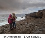 Mother and daughter holding each other and looking at the ocean
