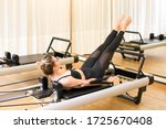 Small photo of Woman performing the hundred pilates exercise on a reformed bed in a gym for core stability, breathing and a cardiovascular workout