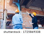 Two engineering man with helmet and paper work are discussing and point at water pipes system on house construction site background - stock photo