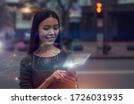 Small photo of Smart city data concept. A beautiful young Asian woman is connected to a public digital network through her nod, mirrored as an augmented reality projection emerging from her phone.