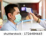 Disease control experts use an Infrared thermometer equipment to check the temperature on the forehead and use alcohol gel to screen the patients addicted to Covid-19 before entering the building. - stock photo