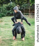 Small photo of two children, boy and girl, playing leapfrog in the garden, active life concept