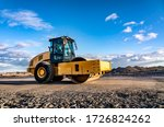 Eye catching yellow road roller with enclosed climate controlled cabin stands on not ready new road, stones, blue sky, clouds, left side view. Clean shiny old heavy tractor