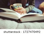 Small photo of Closeup child reading the book at home, girl sitting on the mattress with coffee cup in hand and read the pocket book that rest on the cushion, focus at the book