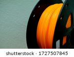 Small photo of Orange plastic filaments with for 3D Printer.3d printing filament spool or coil on holder on green background. Colored plastic material for 3d printer.orange color