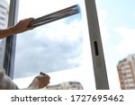 Small photo of tinted glass in the house. window dimming by dark film. hands apply tint film to the window. tint film on sky background. sky view through tinted glass