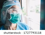 Small photo of Nurse having tired from work while wearing PPE suit for protect coronavirus disease. PPE while protecting healthcare workers from exposure to the COVID-19 virus in healthcare settings.