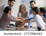Small photo of Diverse workers with mature mentor, putting hands together, showing support and unity after successful presentation at company meeting. Happy female teacher with colleagues in team building activity.
