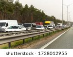Small photo of Highway interstate road with car traffic jam and tree forest on background. Motorway bumber barrier gridlock due country border control point. Vehicle crash accident and queue bottleneck on freeway