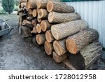 Chopped firewood storage under shed and oak wooden tree logs prepared for chopping and cutting at home backyard. Woodshed store at house yard.Timber material for heating alternative renewable energy - stock photo