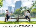 Small photo of Asian young man and woman greet and say hello with they friend and wearing mask sitting distance of 6 feet distance protect from COVID-19 viruses for social distancing for infection risk in park.