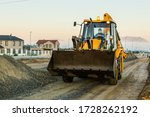 Cape Town, South Africa - May 2020: Bulldozer truck working on construction site early morning sunrise, driver wearing face mask for protection, Corona Virus Pandemic in Africa. - stock photo