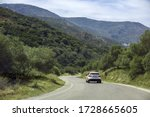 White car slowing down before turning on mountain road. Concept of dangerous roads, low visibility on serpantine roads. - stock photo